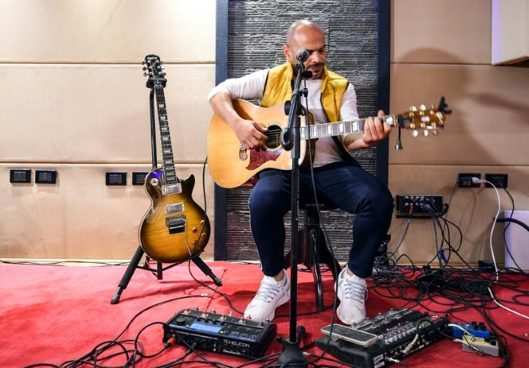 Hani El Dakkak, lead singer and guitarist for Egyptian rock band Massar Egbari, warms up in a recording studio in Cairo