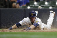 Milwaukee Brewers' Christian Yelich slides in safely at home after tagging up on a sacrifice fly hit by Avisail Garcia during the fifth inning of a baseball game against the New York Mets Friday, Sept. 24, 2021, in Milwaukee. (AP Photo/Aaron Gash)