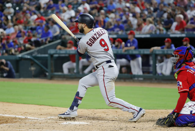Minnesota Twins' Marwin Gonzalez (9) follows through on a run-scoring single in the fourth inning of a baseball game as Texas Rangers catcher Jose Trevino watches in Arlington, Texas, Thursday, Aug. 15, 2019. (AP Photo/Tony Gutierrez)