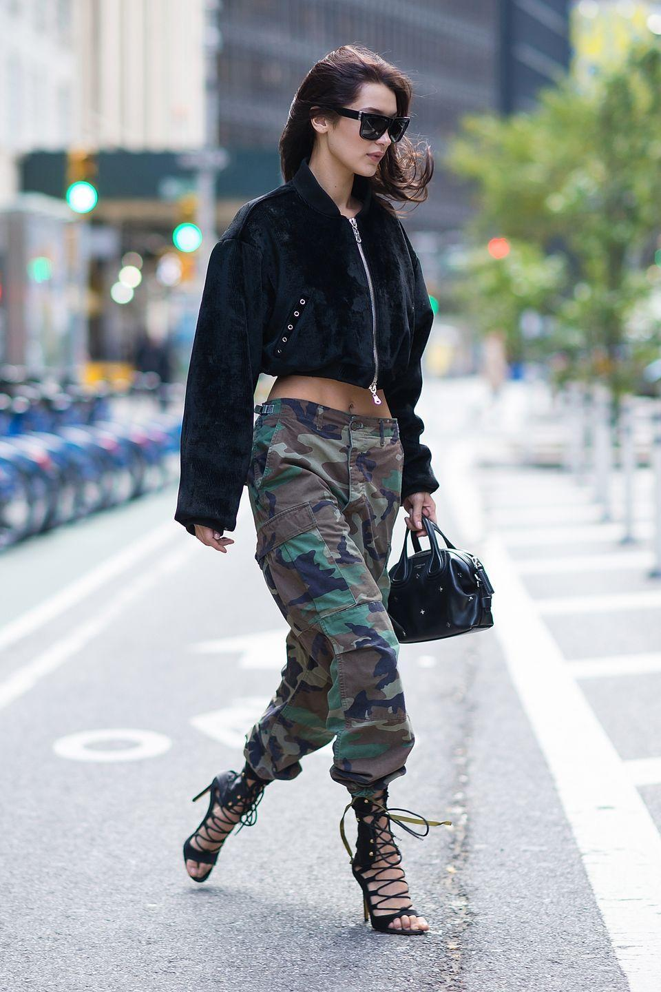 """<p>In camo pants, corduroy bomber, lace-up heeled sandals, a black leather satchel and rectangular sunnies leaving the Victoria's Secret offices—after <a href=""""https://www.harpersbazaar.com/fashion/models/news/a18406/bella-hadid-victorias-secret-fashion-show/"""" rel=""""nofollow noopener"""" target=""""_blank"""" data-ylk=""""slk:landing a coveted spot"""" class=""""link rapid-noclick-resp"""">landing a coveted spot</a> in this year's fashion show. </p>"""