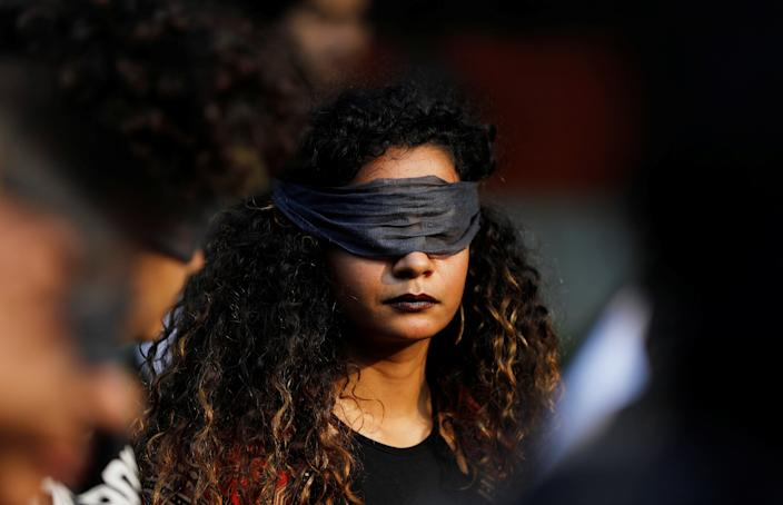 A protestor wearing a blindfold takes part in a protest in solidarity with rape victims and to oppose violence against women in India, in New Delhi, India December 7, 2019. REUTERS/Adnan Abidi - RC2AQD9KST0H