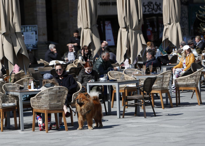 Customers sit outside a cafe in central Belgrade, Serbia, Monday, April 5, 2021, after Serbia eased measures against the coronavirus despite high numbers of infections and a slowdown in vaccinations. The government on Monday allowed bars and restaurants to serve guests outside at reduced capacity and with respect of social distancing rules. (AP Photo/Darko Vojinovic)