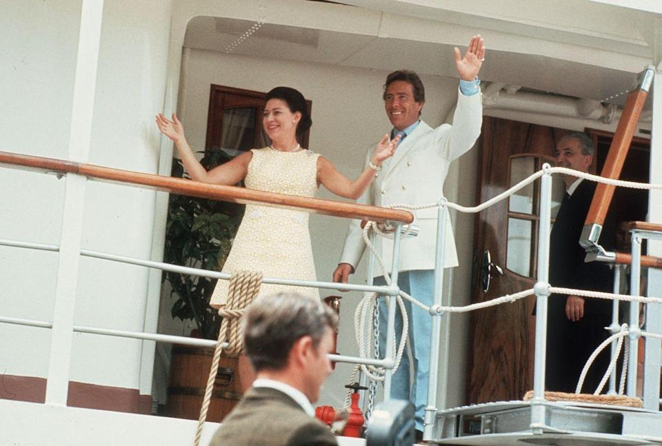 <p>Princess Margaret wears a pale yellow shift dress on the Royal Yacht Britannia. Her husband is dressed just as colorfully in a pair of pale blue pants, a blue shirt, and a white double-breasted blazer. </p>
