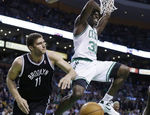 Boston Celtics power forward Brandon Bass (30) dunks over Brooklyn Nets center Brook Lopez (11) during the first quarter of an NBA basketball game in Boston, Wednesday, April 10, 2013. (AP Photo/Elise Amendola)