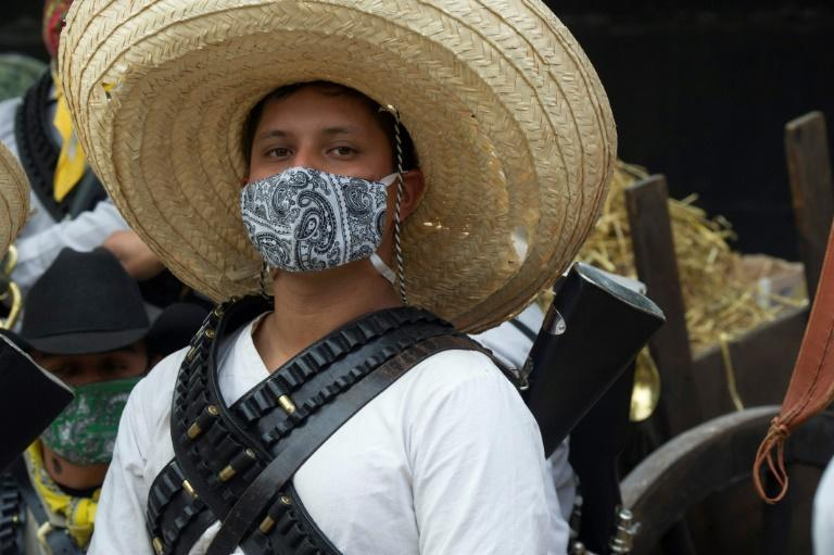 An actor performs wearing a facemask during the commemoration of the 110th anniversary of the Mexican Revolution at the Monument to the Revolution, in Mexico City, on November 20, 2020