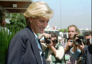"""FILE - In this Thursday, Jan. 16, 1996 file photo, Britain's Princess Diana faces photographers as she leaves Luanda airport building to board a plane to Johannesburg at the end of her four-day visit to Angola. For someone who began her life in the spotlight as """"Shy Di,"""" Princess Diana became an unlikely, revolutionary during her years in the House of Windsor. She helped modernize the monarchy by making it more personal, changing the way the royal family related to people. By interacting more intimately with the public -- kneeling to the level of children, sitting on edge of a patient's hospital bed, writing personal notes to her fans -- she set an example that has been followed by other royals as the monarchy worked to become more human and remain relevant in the 21st century. (AP Photo/Giovanni Deffidenti, File)"""