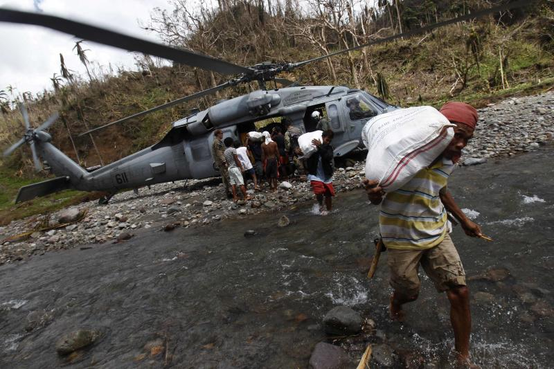 Villagers carry sacks of relief aid as a U.S. helicopter delivers aid to a remote village off Guiuan, Eastern Samar, in central Philippines November 20, 2013. The Philippines is facing an enormous rebuilding task from Typhoon Haiyan, which killed at least 3,974 people and left 1,186 missing, with many isolated communities yet to receive significant aid despite a massive international relief effort. REUTERS/Edgar Su (PHILIPPINES)