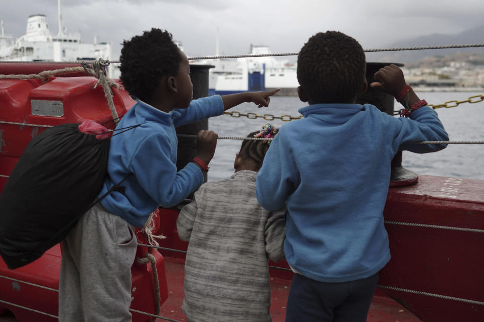 Children wave at a boat from aboard the Ocean Viking as it reaches the port of Messina, Italy, Tuesday, Sept. 24, 2019. The humanitarian ship has docked in Italy to disembark 182 men, women and children rescued in the Mediterranean Sea after fleeing Libya. (AP Photo/Renata Brito)