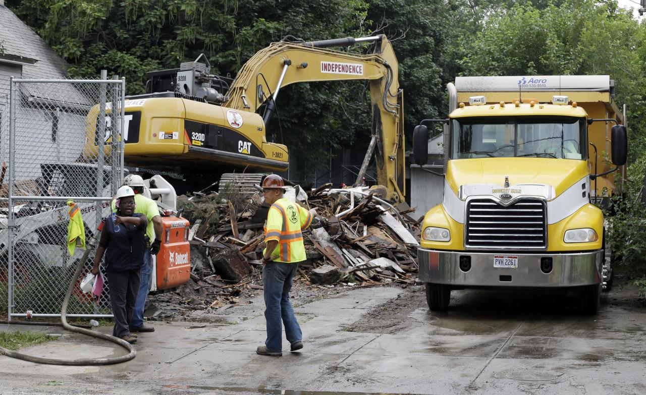 "The house where three women were held captive and raped for more than a decade is demolished, Wednesday, Aug. 7, 2013, in Cleveland. Authorities want to make sure the rubble isn't sold online as ""murderabilia,"" though no one died there. The house was torn down as part of a deal that spared Ariel Castro a possible death sentence. He was sentenced last week to life in prison plus 1,000 years. Castro apologized but blamed his addiction to pornography. (AP Photo/Tony Dejak)"