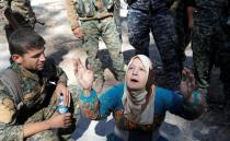 FILE PHOTO: A civilian prays after she was rescued by fighters of Syrian Democratic Forces from the stadium after Raqqa was liberated from the Islamic State militants in Raqqa