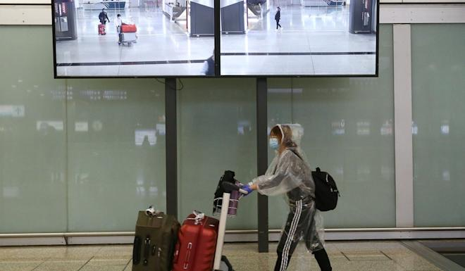 A traveller with her DIY protective gear leaving the airport's arrival hall. Photo: Jonathan Wong