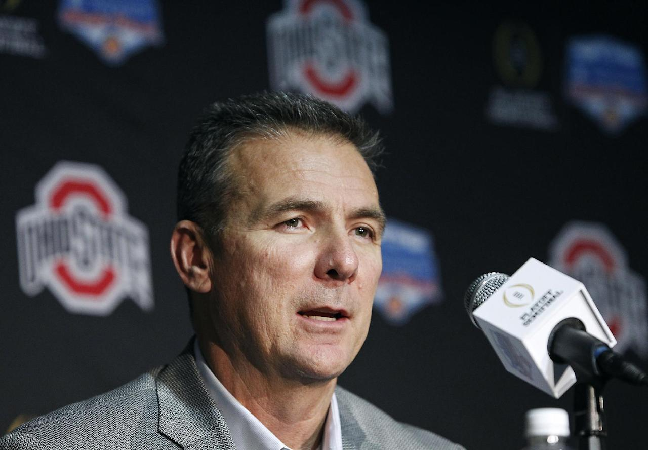 FILE - In this Monday Dec. 26, 2016, file photo, Ohio State head coach Urban Meyer speaks to the media after arriving with his team at Phoenix Sky Harbor Airport in Phoenix. Once seen as a luxury of the corporate world, private planes are becoming increasingly common at U.S. colleges and universities as schools try to attract athletes, raise money and reward coaches with jet-set vacations. At Ohio State University, which leases one plane and partly owns another, Meyer and members of his family took more than 10 personal trips last school year, including a vacation in Florida, a weekend getaway to Cape Cod and a spring break in South Carolina. (AP Photo/Ralph Freso, File)
