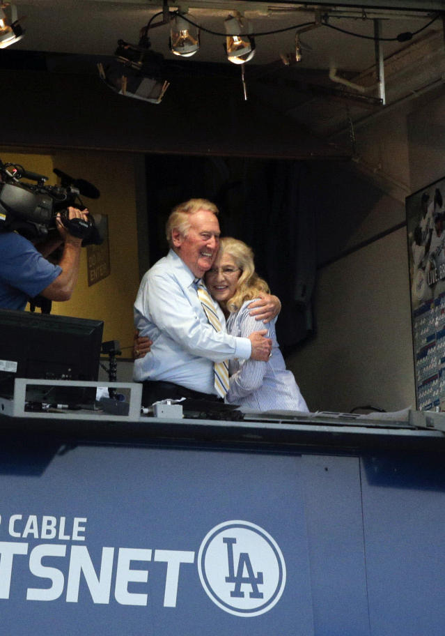 Broadcaster Vin Scully, left, embraces his wife, Sandi, at Dodger Stadium during a baseball game between the Los Angeles Dodgers and the Atlanta Braves on Tuesday, July 29, 2014, in Los Angeles. The Dodgers announced that Scully will remain with the team for the 2015 season. (AP Photo/Jae C. Hong)
