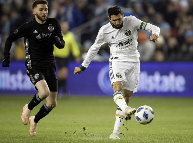 Portland Timbers midfielder Diego Valeri (8) shoots on net ahead of Sporting Kansas City midfielder Ilie Sanchez, left, during the first half in the second leg of the MLS soccer Western Conference championship in Kansas City, Kan., Thursday, Nov. 29, 2018. (AP Photo/Orlin Wagner)
