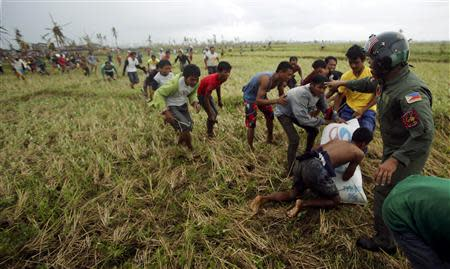 A Philippine Air Force personnel officer (R) tries to push away survivors of Super Typhoon Haiyan from the moving rotor of a helicopter, as its crew deploys aid into a remote area some 25km (17 miles) west of Tacloban cityNovember 17, 2013. The Philippine and U.S. Air Forces are flying rice, clothes and drinking water into remote areas of the central Philippines, which are unreachable by vehicles. REUTERS/Wolfgang Rattay