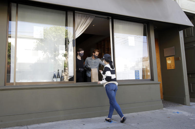 In this Thursday, June 18, 2020, photo, lead sommelier Rachel Coe, left, and service manager Antoine Mueller wear face masks as they assist a customer at the Atelier Crenn restaurant window during the coronavirus outbreak in San Francisco. Some of the world's best restaurants have had to make a quick pivot to weather the coronavirus. (AP Photo/Jeff Chiu)