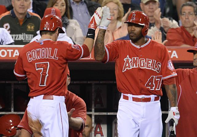 Los Angeles Angels' Collin Cowgill, left, is greeted at the dugout by Los Angeles Angels' Howie Kendrick after scoring a run against the New York Yankees during the third inning of a baseball game in Anaheim, Calif., Tuesday, May 6, 2014. (AP Photo/Jayne Kamin-Oncea)