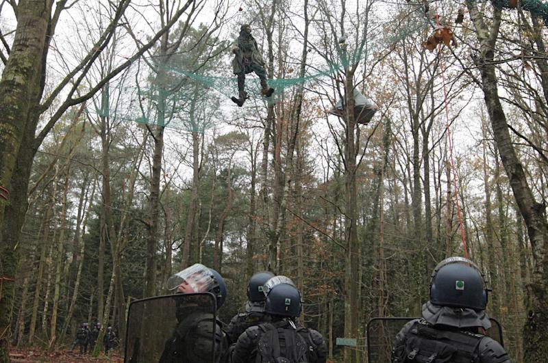 An anti-airport protester looks down at police from a makeshift shelter in the trees during the evacuation of protestors on land that will become the new airport in Notre-Dame-des-Landes, western France Saturday Nov. 24, 2012. The protestors are opposing the building of a new airport there. In a muddy, rainy standoff starting early Friday, protesters responded to police attempts to remove them by hurling sticks, stones and gasoline bombs. For two weeks, protesters have illegally occupied the site of the planned Notre-Dame-Des-Landes airport set to start operating in 2017. (AP Photo/ Laetitia Notarianni)