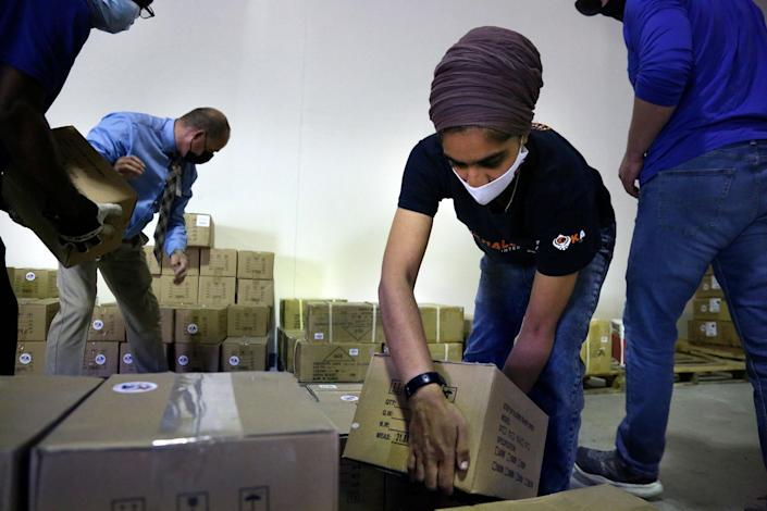 Tim Williams, warehouse assistant for Medisys, Ray Fredericks, assistant director for Medisys, Dr. Abhu Kaur with Khalsa Aid, and Michael Stack, healthcare account representative for Grainger, load dozens of electrical transformers onto a pallet to be shipped from New York to New Delhi, along with oxygen concentrators, on May 7, 2021.