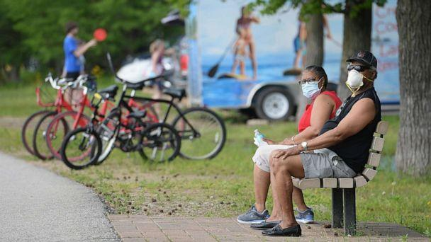 PHOTO: A man and woman sit with their masks on at Creve Coeur Lake Park on May 25, 2020 in Maryland Heights, Missouri. (Michael Thomas/Getty Images)