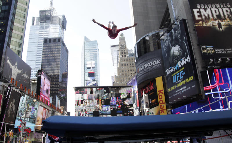 Gymnast Alaina Williams performs on a trampoline in New York's Times Square during U.S. Olympic Team festivities, Wednesday, April 18, 2012. The event marks 100 days until the London Olympics. (AP Photo/Bebeto Matthews)