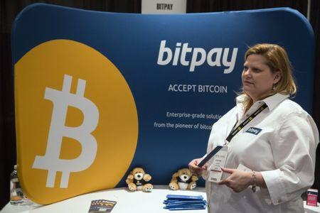 A woman explains how bitpay, a company designed to help companies use virtual currency, to attendee during Inside Bitcoins: The Future of Virtual Currency Conference in New York