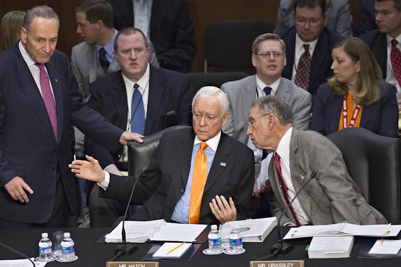 FILE – In this May 9, 2013, file photo Sen. Orrin G. Hatch, R-Utah, confers with Sen. Chuck Grassley, R-Iowa, right, and Sen. Chuck Schumer, D-N.Y., left, as the Senate Judiciary Committee meets to address immigration reform on Capitol Hill in Washington. More than any other group, the high-tech industry got big wins in the immigration bill  approved last week. It amounted to a bonanza for the industry, granting unlimited green cards to foreigners with certain advanced U.S. degrees, and greatly boosting visas for highly skilled foreign workers. And thanks to Hatch's intervention, the industry succeeded in greatly curtailing controls sought by Sen. Dick Durbin, D-Ill., not shown, who aimed to protect U.S. workers.  (AP Photo/J. Scott Applewhite, File)