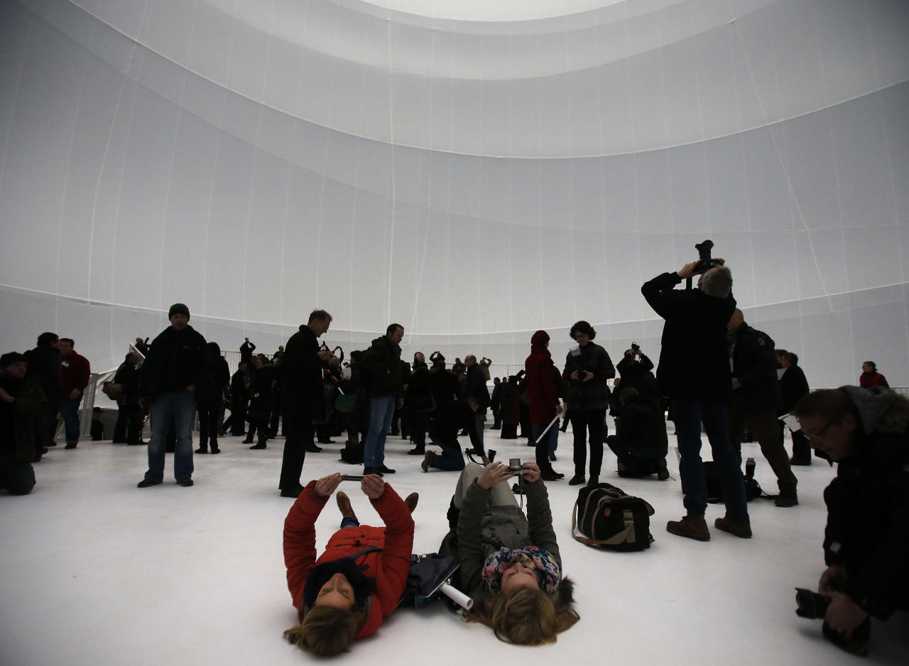 Visitors take pictures inside the installation 'Big Air Package' during the unveiling at the Gasometer in Oberhausen, Germany, Friday, March 15, 2013. Christo's latest monumental sculpture in the interior of the industrial monument can be seen from March 16 until Dec. 30, 2013. (AP Photo/Frank Augstein)