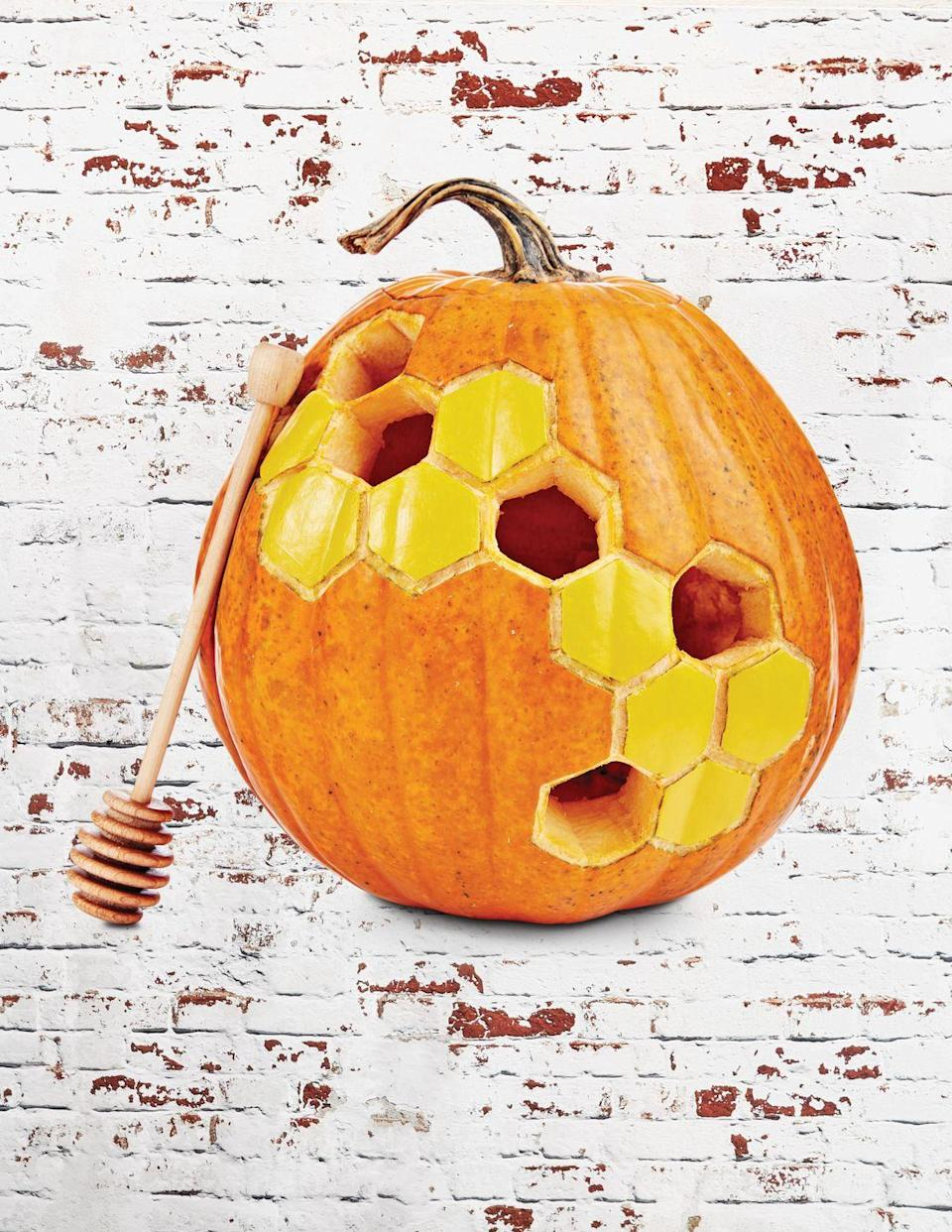 """<p>It's cute, fun, and just a little bit different. This honeycomb pumpkin is an easy alternative to the more intricate <a href=""""https://www.countryliving.com/diy-crafts/g279/pumpkin-carving-ideas/"""" rel=""""nofollow noopener"""" target=""""_blank"""" data-ylk=""""slk:carving"""" class=""""link rapid-noclick-resp"""">carving</a> designs out there.</p><p><strong>Make the honeycomb pumpkin:</strong> Cut a hole in the bottom of a medium orange pumpkin; scoop out pulp and seeds. Draw a honeycomb pattern on the front; etch out. Cut out a few of the combs and paint the remaining combs with yellow craft paint. Lean a honey dipper against its side. </p>"""