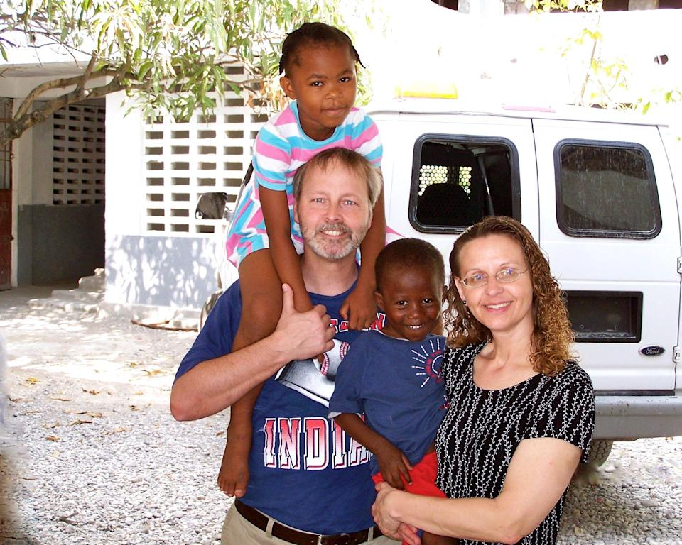 Rev. Chuck Whited and his wife Susan in Haiti in 2004 with the children they would later adopt, Lovelie and Wisken.