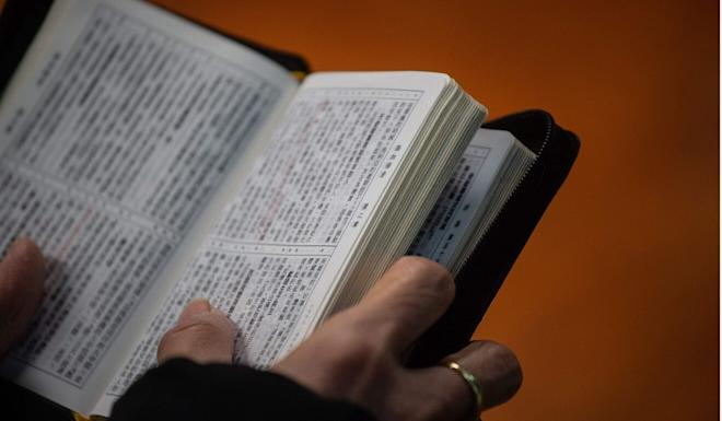 A worshipper holds a copy of the Bible. Photo: AFP