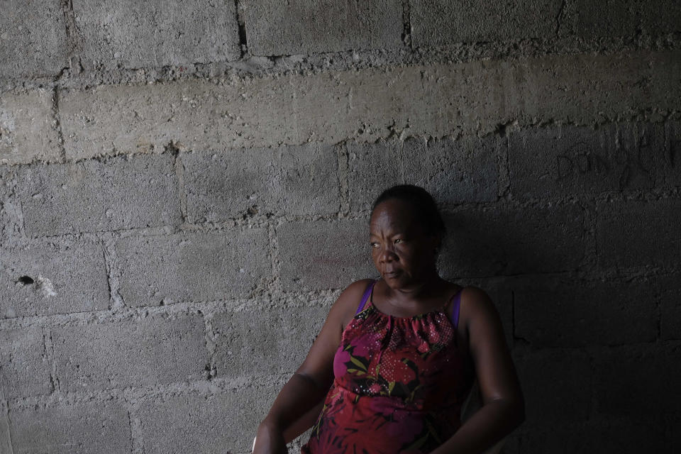 Nurse Gabrielle Lagrenade rests next to a wall in Les Cayes, Haiti, Monday, Aug. 23, 2021, a week after a 7.2 magnitude earthquake made her rental home unsafe to live in. Lagrenade is not unsympathetic to the plight of her newly homeless patients, as she herself sleeps outside. (AP Photo/Matias Delacroix)