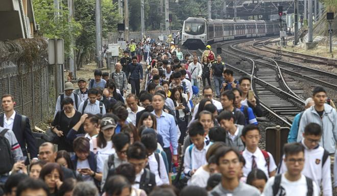 Some commuters had to walk after a train was halted by objects on the track. Photo: Winson Wong