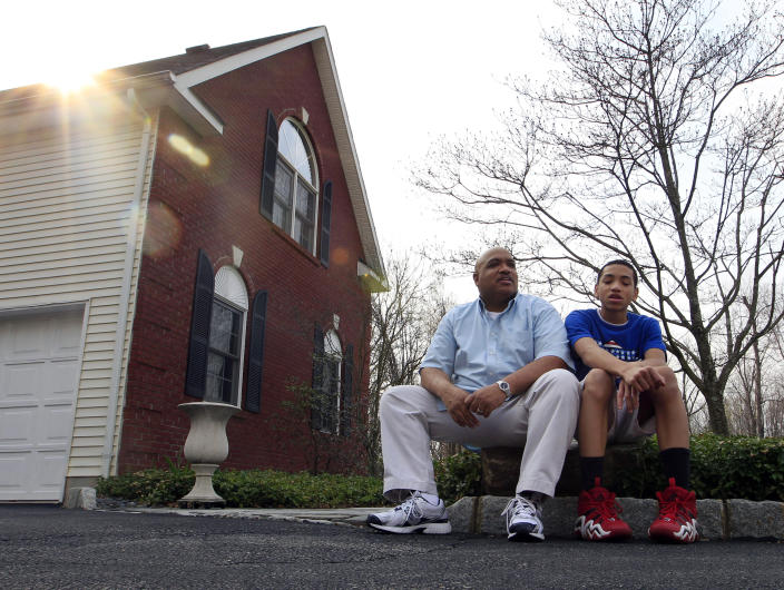"In this Friday, March 23, 2012 photo, Bill Stephney talks to his son Trevor, 13, as they sit outside their home in Randolph Township, N.J. Stephney, a media executive who lives in a New Jersey suburb that is mostly white and Asian, has two sons, ages 18 and 13. The killing of Trayvon Martin was an opportunity for him to repeat a longtime lesson: black men can get singled out, ""so please conduct yourself accordingly."" (AP Photo/Mel Evans)"
