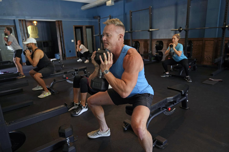 Scott Johnson, foreground in blue, participates in a fitness class at Lift Society Friday, May 21, 2021, in Studio City, Calif. California's top health official says the state no longer will require social distancing and will allow full capacity for businesses when the state reopens on June 15. (AP Photo/Marcio Jose Sanchez)