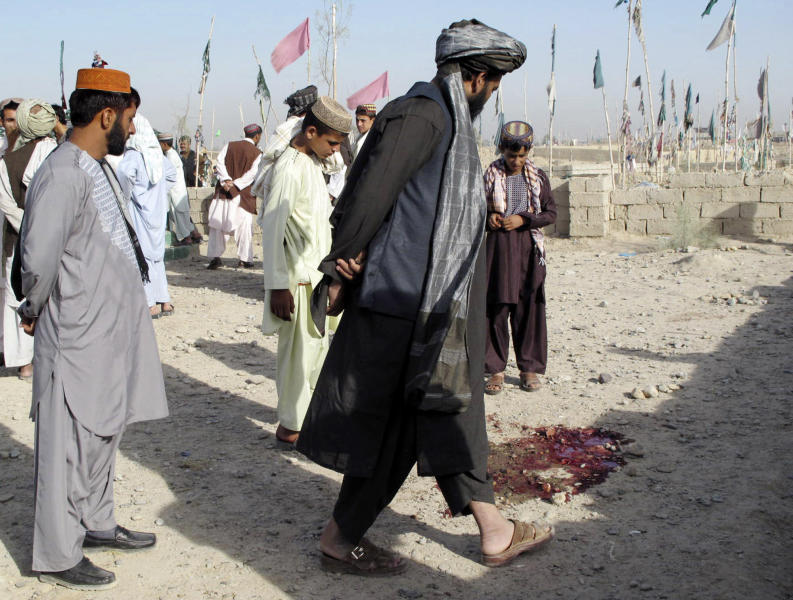 Afghans look at a pool of blood at the scene of an explosion at a cemetery in Lashkar Gah southwest of Kabul, Afghanistan, Sunday, Aug. 19, 2012. A bomb hidden in the cemetery exploded Sunday as a police official and his family were visiting the grave of a relative, killing the official and his brother, police said. (AP Photo/Abdul Khaleq)