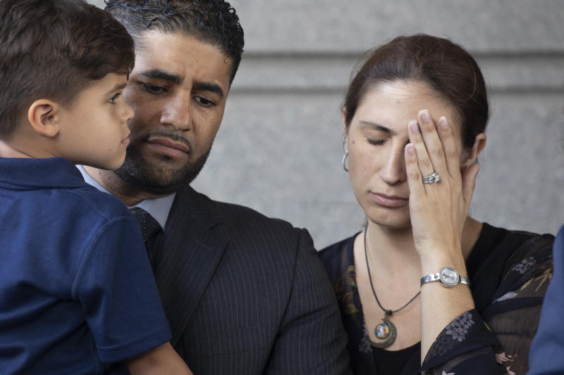 Juan Rodriguez, holding his son Tristan, leaves Bronx Criminal Court with his wife Marissa after a hearing, Thursday, Aug. 1, 2019 in New York. Rodriguez has pleaded not guilty to manslaughter and other charges in the deaths of their 1-year-old twins left in a car on Friday while he put in a day at work. Prosecutors say Rodriguez told police he thought he had dropped the twins off at day care. (AP Photo/Mark Lennihan)
