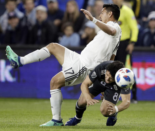 Sporting Kansas City midfielder Roger Espinoza (17) and Vancouver Whitecaps midfielder Felipe Martins (8) battle for the ball during the first half of an MLS soccer match in Kansas City, Kan., Friday, April 20, 2018. (AP Photo/Orlin Wagner)