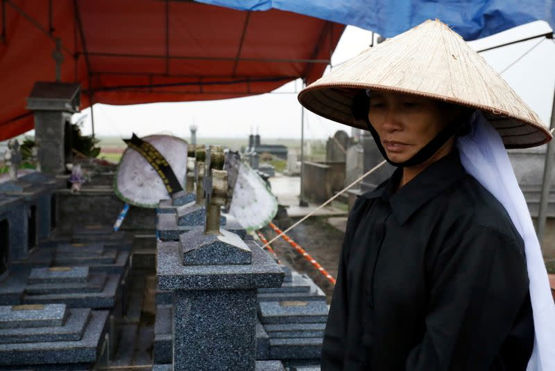 Nguyen Thi Huan visits the newly built grave of her son Nguyen Dinh Luong, a victim who was found dead in the back of British truck, at the homeland cemetery in Ha Tinh province