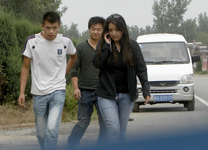 FILE - In this Sept. 9, 2010 file photo, unidentified Chinese men escort a foreign television journalist after they blocked a road at the entrance to Dongshigu Village, in Yinan county, China. Suddenly the guard posts came down and the hired toughs who manned them melted away, restoring an air of freedom this week to the village that authorities turned into a prison to keep blind activist Chen Guangcheng under house arrest for nearly two years. (AP Photo/Andy Wong, File)