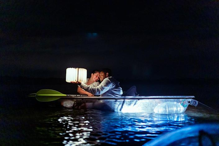 Couple in a clear-bottom kayaks in the bioluminescence water