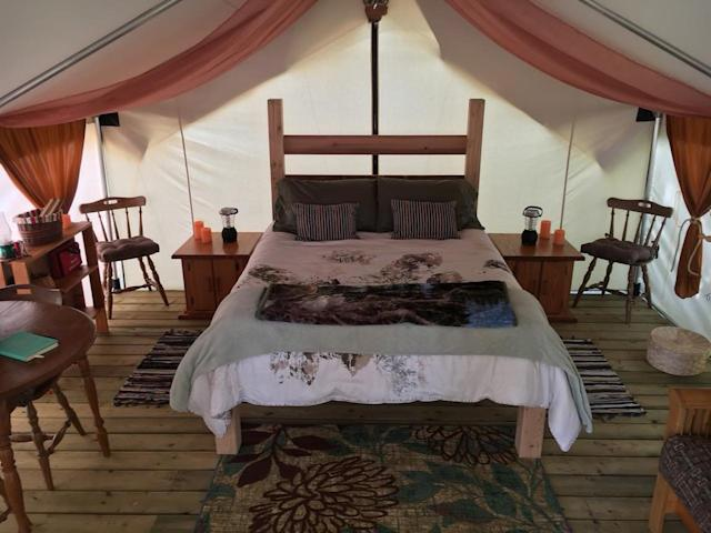 "<p>This isn't any ordinary tent, though. You'll be ""glamping,"" sleeping in a handmade queen bed. (Airbnb) </p>"