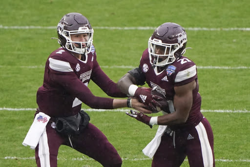 Mississippi State quarterback Will Rogers (2) hands the ball to running back Jo'Quavious Marks (21) against Tulsa during the first half of the Armed Forces Bowl NCAA college football game Thursday, Dec. 31, 2020, in Fort Worth, Texas. (AP Photo/Jim Cowsert)