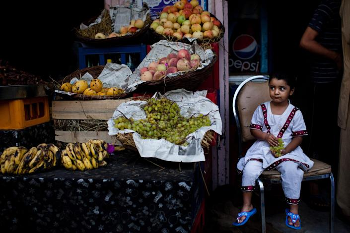 A girl looks on as she sits at a fruit stall prior to 'Iftar', when Muslims break their fast, on the third day of the holy month of Ramadan on August 4, 2011 in Rawalpindi, Pakistan. Ramadan, the month in which the holy Quran was revealed to the prophet Mohammad, is observed by devout Muslims who abstain from food, drink and sex from dawn until sunset, when they break the fast with the meal known as Iftar. (Photo by Daniel Berehulak/Getty Images)