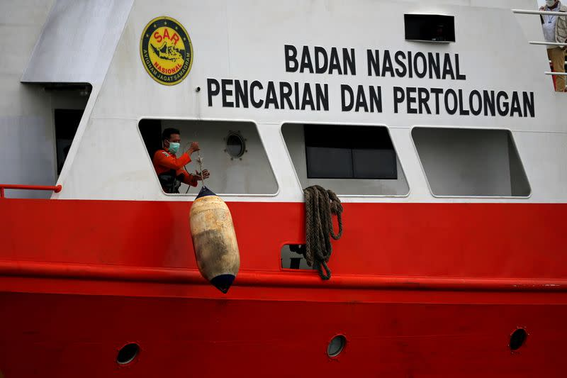 A rescue worker is seen onboard Indonesian Search and Rescue Agency's ship during a recovery operation for Sriwijaya Air flight SJ 182 at Tanjung Priok port in Jakarta