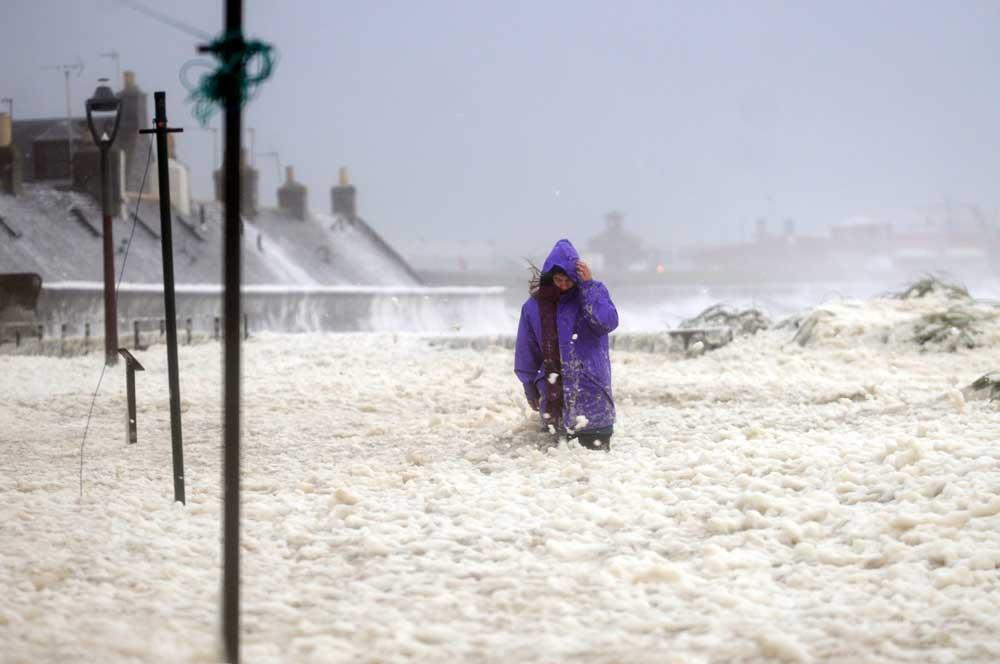 Walking through deep foam ...... A woman makes her way through South Square in Fittie on the coast at Aberdeen, that has been covered in a thick sea foam after flooding from the North sea as the stromy weather continues along the Scottish coast.