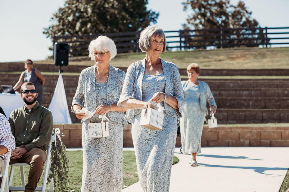 The 'flower girls' sprinkled petals as they walked down the aisle [Photo: Natalie Caho Photography]