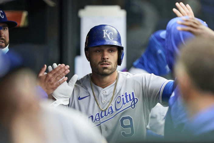 Kansas City Royals' Ryan McBroom is congratulated by teammates after scoring in the seventh inning of a baseball game against the Cleveland Indians, Monday, April 5, 2021, in Cleveland. (AP Photo/Tony Dejak)