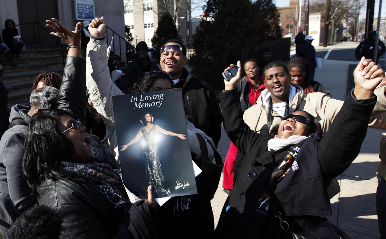 Fans sing Whitney Houston songs as they gather a few blocks from the New Hope Baptist Church before the singer's funeral in Newark, N.J., Saturday, Feb. 18, 2012. (AP Photo/Jason DeCrow)