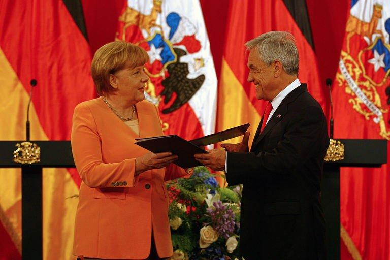 German Chancellor Angela Merkel (L) and Chilean President Sebastian Pinera, exchange documents during a ceremony at La Moneda presidential palace in Santiago as part of her official visit to Chile in the framework of the Community of Latin American and Caribbean States (CELAC)-European Union (EU) Summit, on January 26, 2013